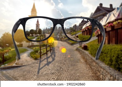 A view through black-rimmed vision glasses with anti-glare glass of a small, beautiful city. Vision glasses concept.