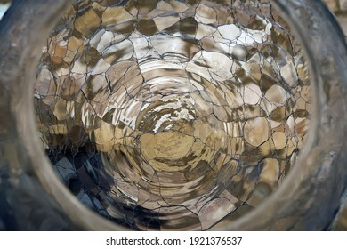View of through bottom of cracked glass vase of a brick wall. Ethereal abstract background texture and pattern. Light fractured, refracted and distorted. Concentric circles or ripples of light.