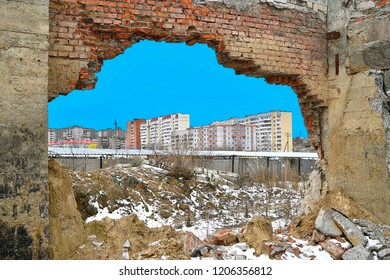 View through the break in the wall of the red brick of the old building on the built-up quarter of the city.