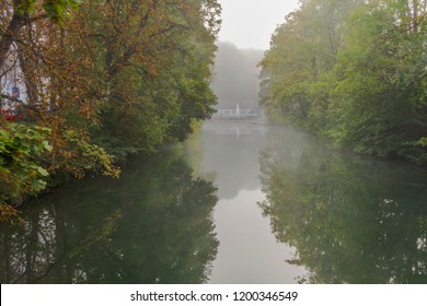 View through bushes over mist-covered water on the city wall of the city Augsburg with the moat at the oblatter wall