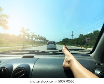 View through car windshield on highway with palm trees and blue sky