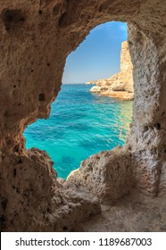 View through the cave window at A Boneca Cliff at the Carvoeiro Boardwalk at the Algarve coast near Lagoa