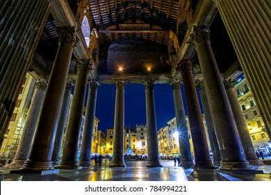 View through the columns of the Ancient Roman Pantheon to the Fountain of the Pantheon placed in Piazza della Rotonda at night, Rome, Italy. Low angle view