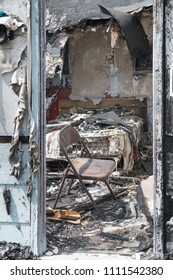 View through the door into a burned out bedroom with a mattress and folding chair