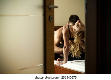 View through the door of young caught couple during foreplay