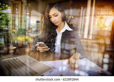 View through glass Asian businesswomanwith digital tablet, businesswoman running a coffee shop.