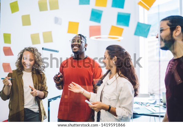 View through glass board of laughing multiethnic men and women creating new strategy and placing colorful sticky notes making project