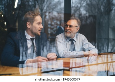 View through glass of cheerful mature businessman sitting at table with younger male colleague and discussing project details in daylight