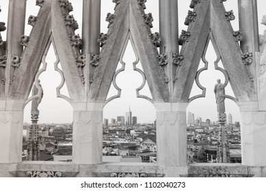 A view through the gothic windows from the roof of Milano Duomo on the modern city of Milano