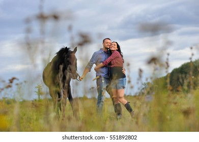 View through the grass: young couple - she is handsome brunette with long hair, pregnant; he is tall and brave, holding the reins of the black horse, a walk on the meadow. Wonderful sky behind them