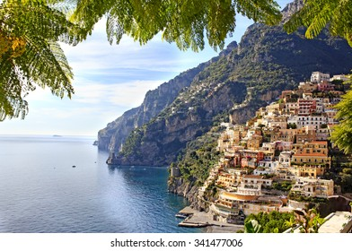 View through green leaves on the Colorful Positano town, the most famous place of the Amalfi Coast, South of Italy.