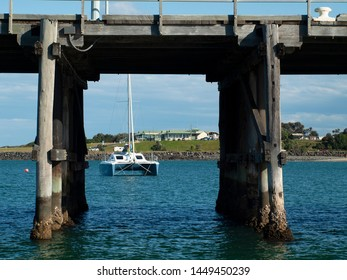 View through an historical timber waterfront pier/dock with catamiran boat in tropical water with cloudy blue sky backdrop. Safe harbour for sailing and cruising vessels. Coffs Harbour, Australia.