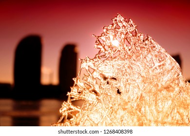 View through the ice floe at sunset and the city,textured ice floe on the background of sunset and cityscape