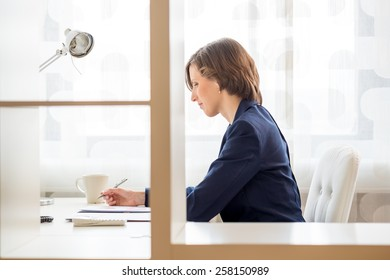 View through an interior glass partition of a businesswoman working in an office sitting at her desk in profile.
