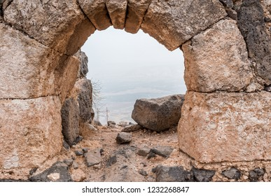 view through the loophole of the ancient crusader fortress in the mountains