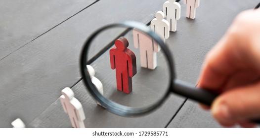 Der Blick durch die Lupe auf der einen hölzernen roten Person zwischen den anderen Leuten
