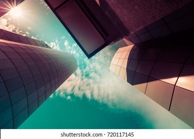 View through modern high rising skyscrapers upwards to blue sky with white clouds. Abstract architecture detail background in turquoise teal blue to burgundy purple pastel colors