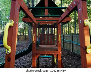 View through the monkey bars of a wooden backyard play set.