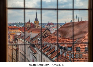 View through old tower window on Prague old town roofs