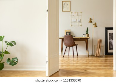 View through an open door into an artist's workspace interior with a vintage, leather chair, kraft paper and white walls