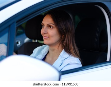 View through the open side window of an attractive female driver in a car