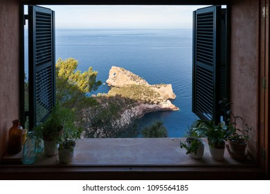 View through an open window of the Punta de  Sa Foradada Peninsula in Deia, Mallorca.