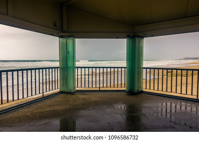 View through open windows of an empty beach in a overcast day