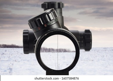 view through an optical sight at the winter snow field