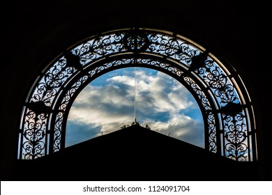View through ornated door to cloudy sky