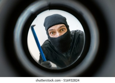 View through peephole. Thief or burglar masked with balaclava is holding crowbar behind the door.