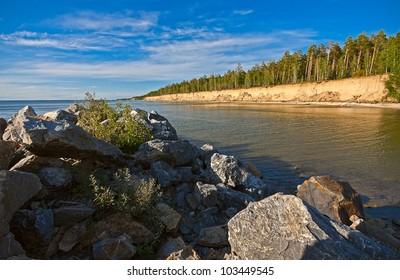 View through rocks on coastline of beach of sea, Russia.