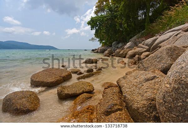 View through rocks on coastline of beach of sea,Thailand .