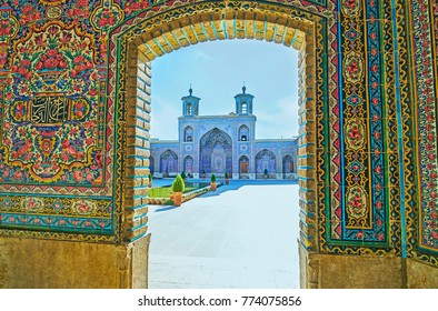 The view through the scenic tiled doorway on the portal of Nasir Ol-Molk mosque and the fountain in front of it, Shiraz, Iran.