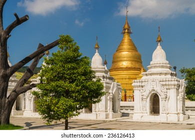 View through some white stupas to the golden Kuthodaw Pagoda in Mandalay. 729  stupas with a marble slab inscribed on both sides surround the main pagoda, such making it the largest book in the world.