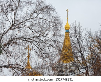 View through the tree branches to the golden domes and crosses of the Orthodox Church. Late fall. Beautiful bell tower. Ascension Cathedral, Novosibirsk, Siberia, Russia. Perfect for background.