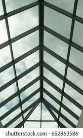 A view through a triangular arched glass roof to the overcast sky, white aluminum frames, double-glazed windows. Photo partially toned