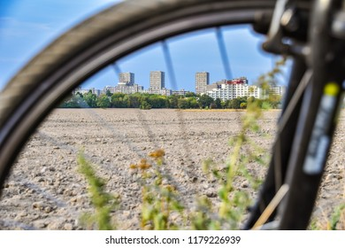 View through the unfocused front wheel of a bicycle across a field to the satellite town of Gropiusstadt in Berlin-Neukölln.