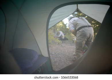 View through the unzipped flap from inside a tent of the campsite outside with two men preparing for the days activities