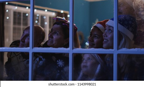 View through window of big happy family looking away in window and watching fireworks on Christmas celebration