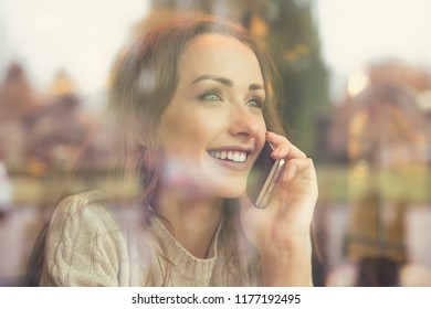 View through window of coffee shop of young happy woman having phone call and smiling away