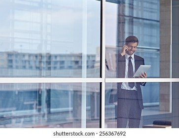 View through a window of a corporate executive talking on his phone and looking at a digital tablet