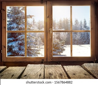 View through the window of a cottage into a snow-covered winter forest