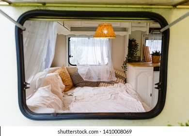 View through the window into the interior of the camper van. Unmade bed, pillows, white wooden interior with lamp center. Cozy sleeping place for a young couple to sleep inside a camper for traveling