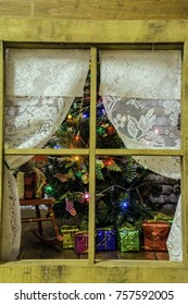 view through window with lace curtains of decorated Christmas tree surrounded by assorted presents on wood floor
