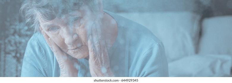 View through window of older woman having headache or migraine