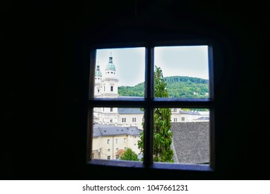 View through window over buildings and church dome to green hills beyond from catacombs in Salzburg, Austria