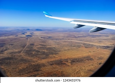 View through the window of a passenger plane flying above Namibia, Africa, taken just a minute before landing at the Windhoek Airport