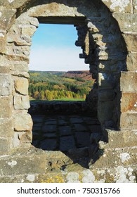 View through a window of the ruins of Skelton Tower near Levisham on a bright, sunny autumn day with views over North York Moors National Park, Yorkshire, UK
