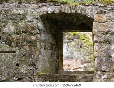 view through a window in the wall of the ruins of an old water mill made of natural stone in the forest near Dolny Mlyn in Bohemian Switzerland national park