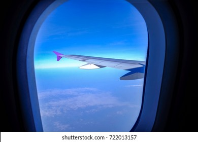 View through the window, which sees wings of planes flying over the sky and clouds.